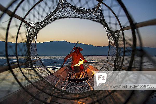 Intha leg rowing fisherman viewed through net on Inle Lake  Shan State  Myanmar (Burma)