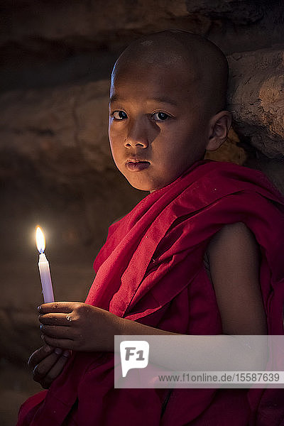 A young Buddhist monk holding candle at temple  Bagan (Pagan)  Myanmar (Burma)