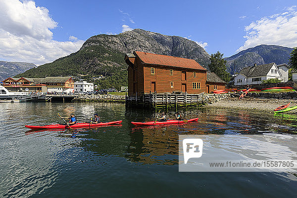 Sea kayakers head off  beautiful Eidfjord village  mountains and beach  sunny day  Norwegian Western Fjords  Norway  Scandinavia