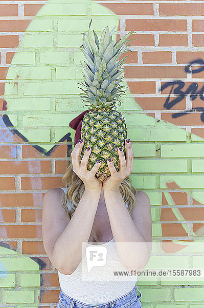 Portrait of young blond woman with ananas in front of her face