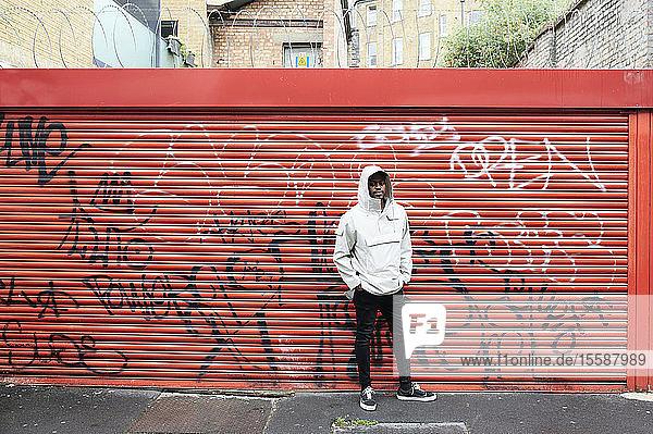 Man wearing rainjacket standing in front of graffiti on roller shutter