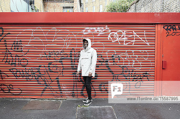 Laughing man wearing rainjacket standing in front of graffiti on roller shutter