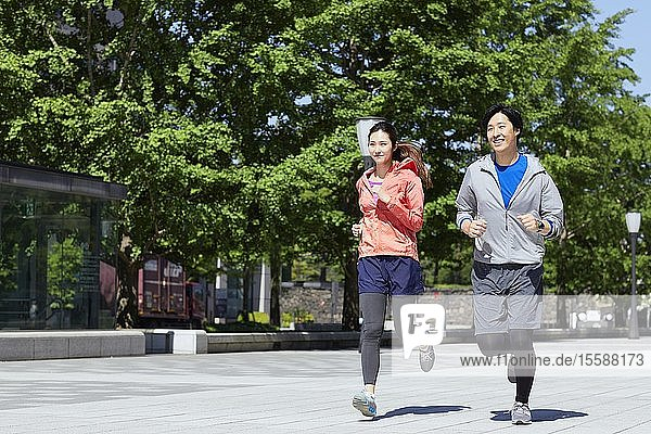 Young Japanese couple running downtown Tokyo