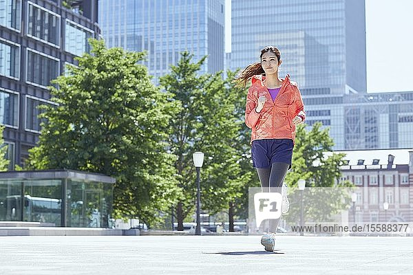 Young Japanese woman running downtown Tokyo