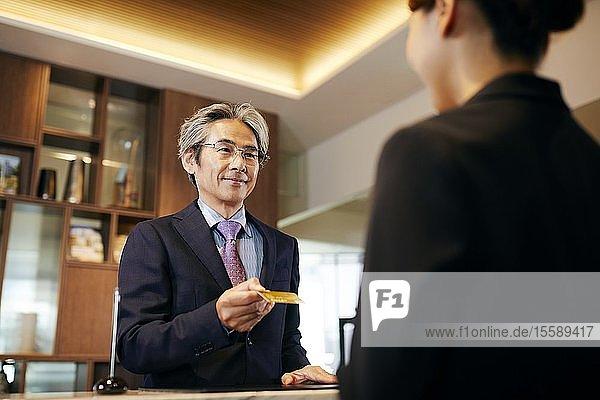 Senior businessman checking in at hotel
