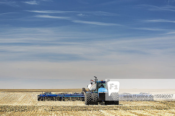 Tractor with air seeder  seeding a stubble field with blue sky and hazy clouds  near Beiseker; Alberta  Canada
