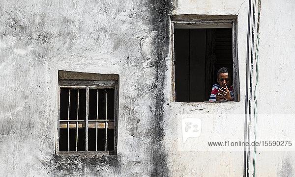 Boy in window holding smart phone  Stone Town of Zanzibar; Zanzibar City  Unguja Island  Zanzibar  Tanzania
