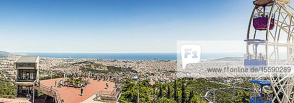 Amusement park with a colourful ferris wheel on Mount Tibidabo and a view of the Mediterranean Sea; Barcelona  Catalonia  Spain