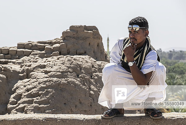 Young Sudanese man posing with confidence while crouching on a rock wall; Kerma  Northern State  Sudan