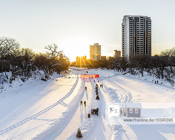 Ice skating at sunset on the Assiniboine River  part of the Red River Mutual Trail at The Forks; Winnipeg  Manitoba  Canada