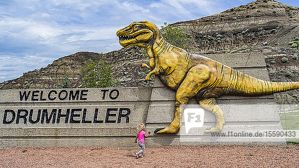 Large sign 'Welcome to Drumheller' with dinosaur and young girl running towards it; Drumheller  Alberta  Canada