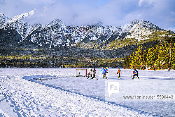 Frozen Pyramid Lake with kids playing hockey on a cleared ice rink in winter  Jasper National Park; Alberta  Canada