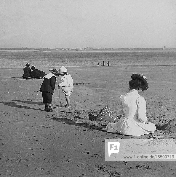 Magic Lantern slide circa 1880  Victorian/Edwardian  social history. Beach scene with children playing and adults sitting in the sun. The children have built a sandcastle.