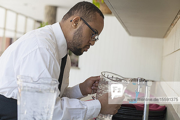 African American man with Down Syndrome as a waiter filling jug of water in kitchen