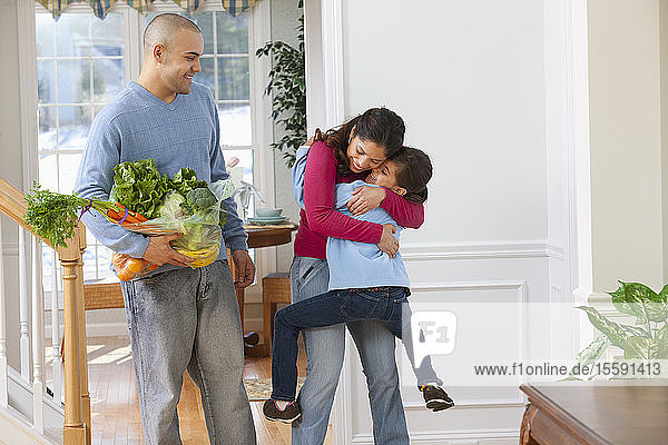 Hispanic woman hugging her daughter with her husband standing beside her