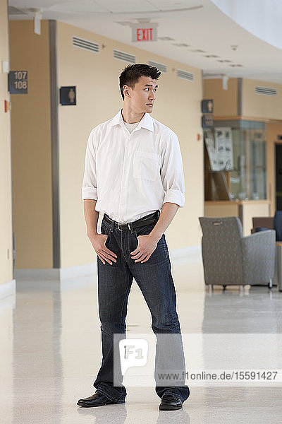 Student standing with hands in his pockets