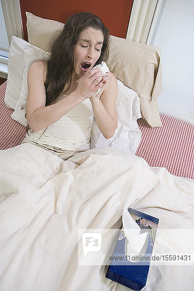 High angle view of a mid adult woman sitting on the bed and sneezing