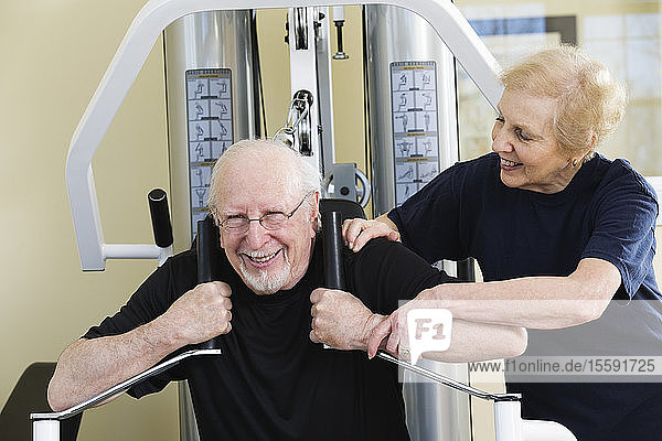Senior couple working out on exercise equipment in a gym