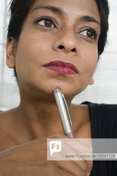 Close up of a business woman with a pen.