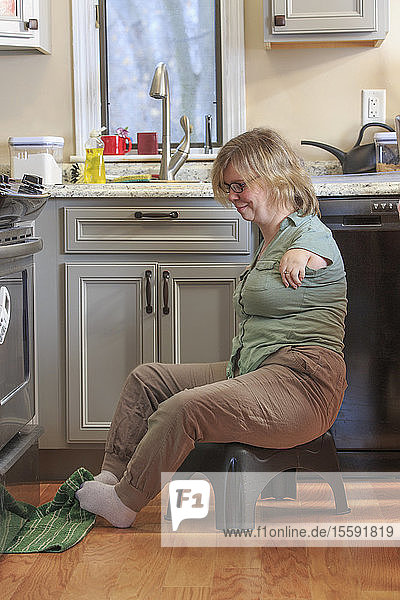 Woman with TAR Syndrome picking up a kitchen towel with her feet