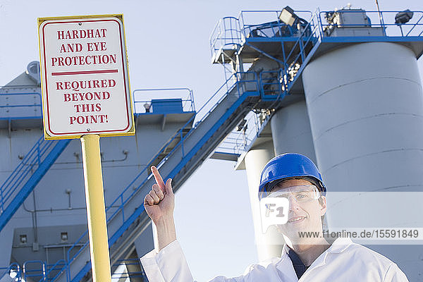 Lab worker pointing at a warning sign saying 'Hardhat and Eye Protection Required Beyond This Point' at an asphalt plant