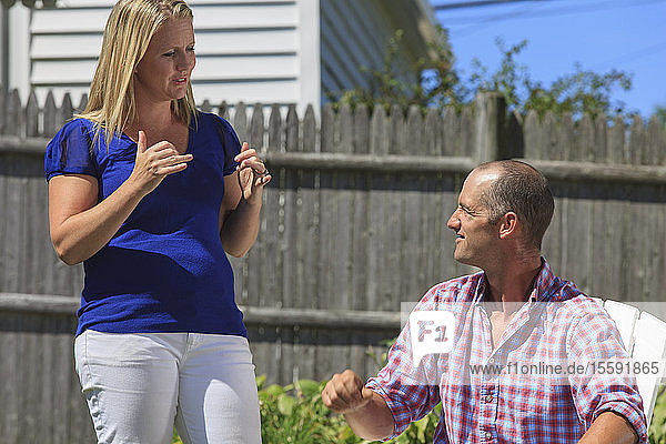Husband and wife with hearing impairments signing 'play  yes' in American sign language