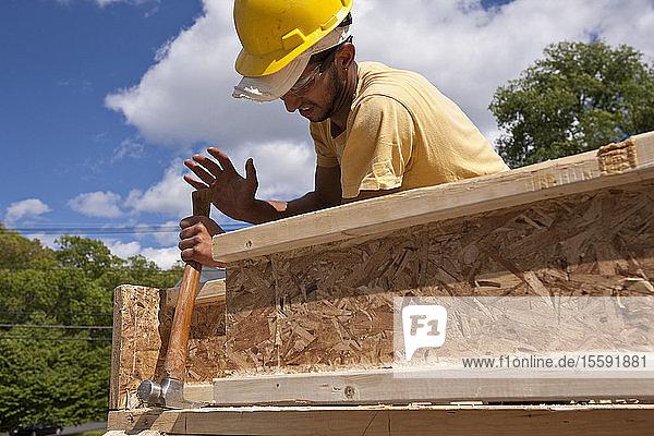 Carpenter using framing hammer on a house frame