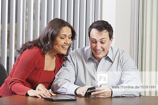 Geschäftspaar nutzt Tablet und Smartphone