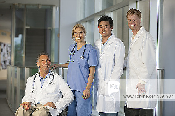 Hospital staff standing beside a doctor in wheelchair with spinal cord injury