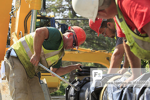 Construction workers using torque wrench to secure water main section with bolts