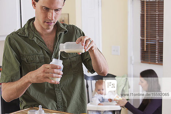 Father preparing baby's formula and mother feeding baby