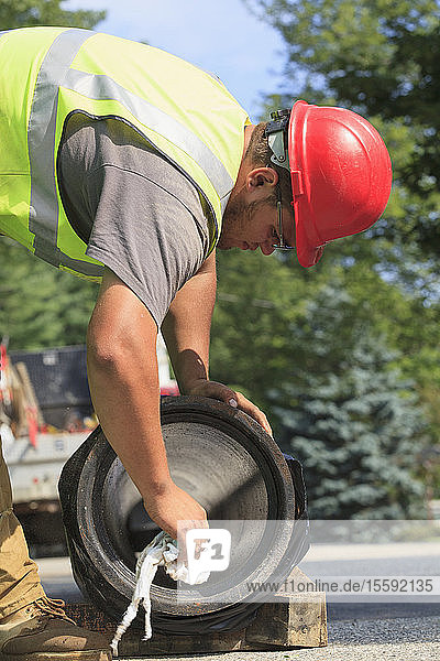 Construction worker preparing water main for installation