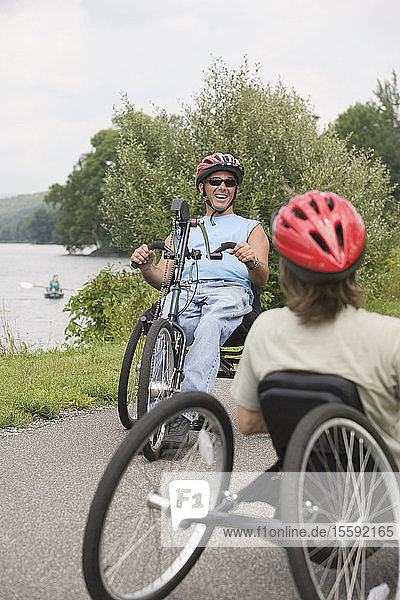 Young man with a Spinal Cord Injury and a young woman riding adaptive bikes