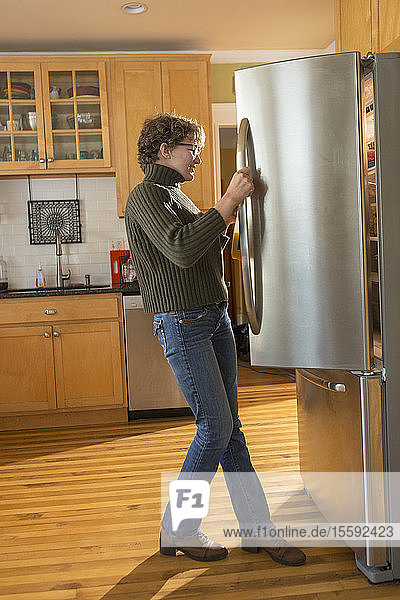 Woman with Sjogren-Larsson Syndrome opening refrigerator