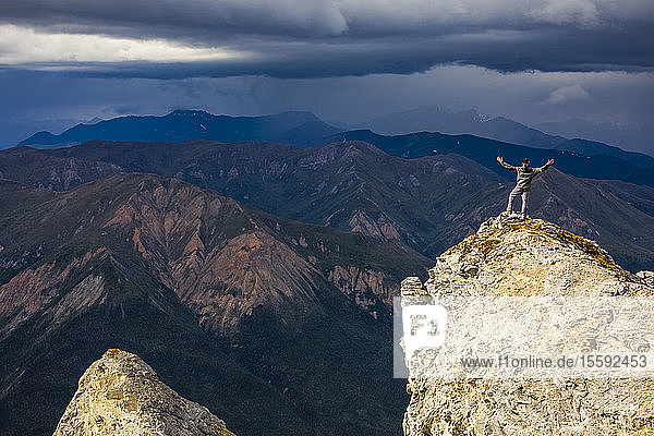 Sunshine illuminates a hiker on top of Sukakpak Mountain as storm clouds brew in the distance over the Brooks Range; Alaska  United States of America