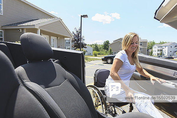 Woman with spinal cord injury in wheelchair entering in her adaptive car