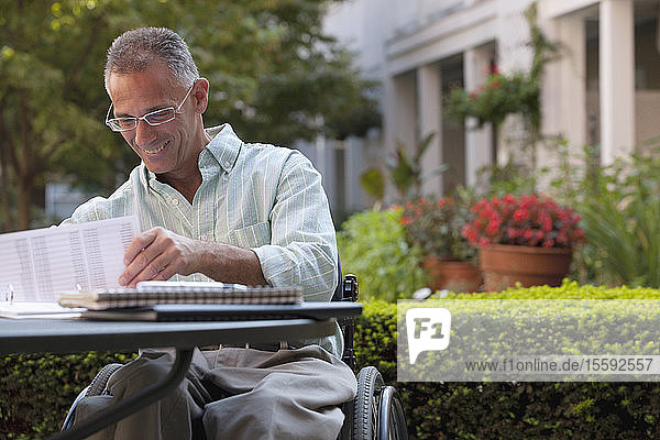 Businessman with spinal cord injury working on documents at a café