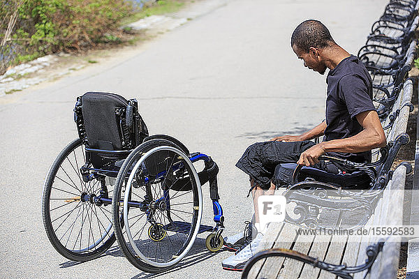 Man who had Spinal Meningitis with a wheelchair relaxing in a park