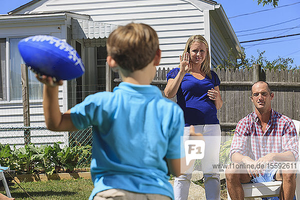 Family with hearing impairments playing football and signing in American sign language in backyard