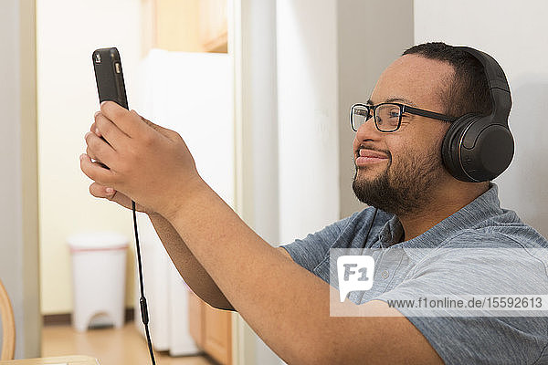 Happy African American man with Down Syndrome listening to music on phone with headphones at home