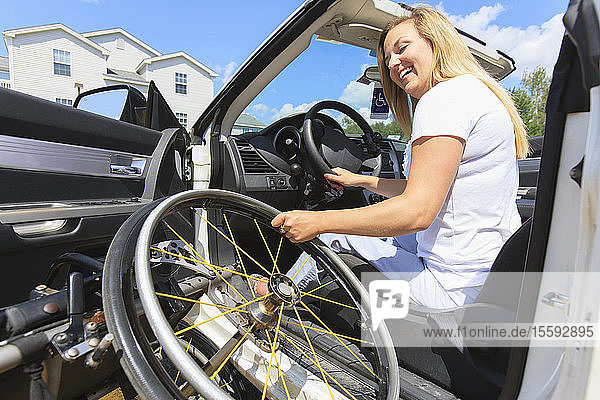 Woman with a spinal cord injury putting her wheelchair into her adaptive vehicle