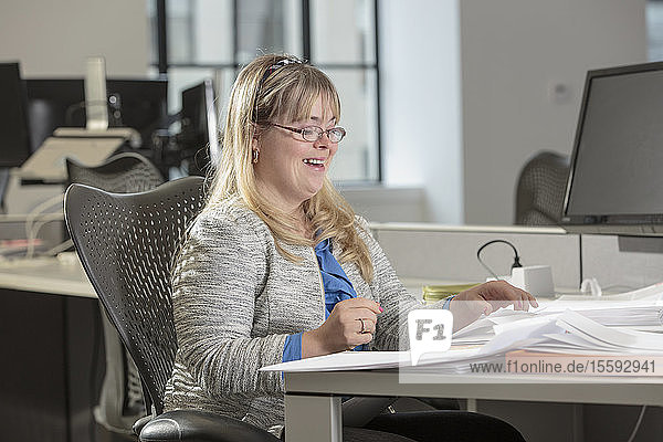 Young woman with Down Syndrome doing paperwork in an office