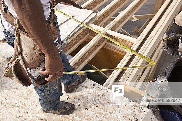 Carpenter holding a tape measure