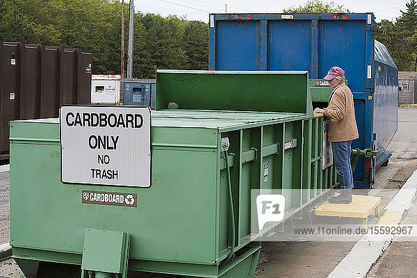 Woman doing recycling at Cardboard Only recycling compactor connected to container