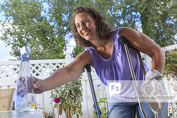 Woman with Spina Bifida on crutches about to clean patio table