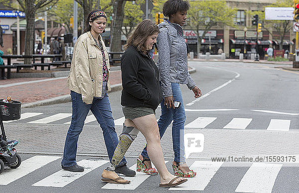 Four female friends with disabilities crossing a street