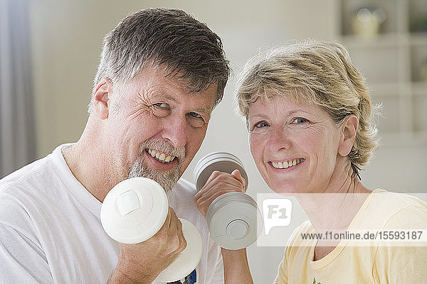 Portrait of a senior couple exercising with hand weights and smiling
