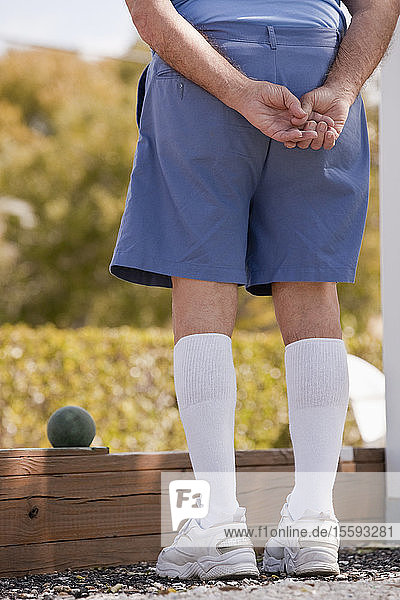 Rear view of a man watching a bocce ball game