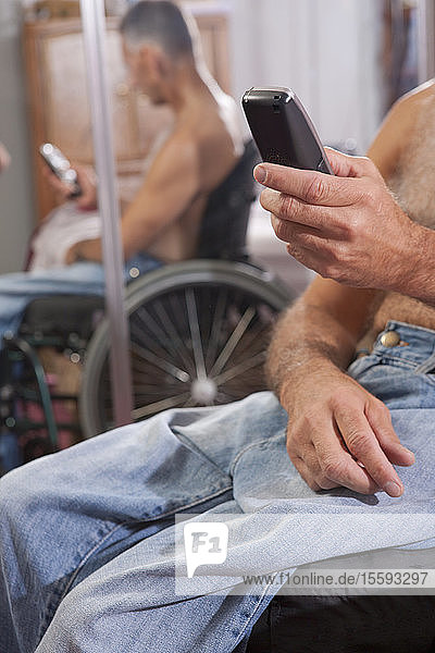 Man with spinal cord injury in a wheelchair using a mobile phone