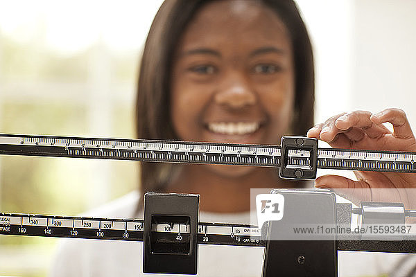 Smiling teenage girl adjusting the slide on a medical weight scale.